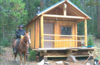 The range rider next to 'Horsethief Cabin' that was built with help from Defenders (Photo: Mel Mckitrick)